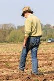 Ein gehendes Erntefeld des Landwirts bereit, an pflügendem Match zu pflügen Lizenzfreie Stockfotos