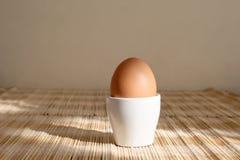 Ein gekochtes Ei in einem Eierbecher stockbild