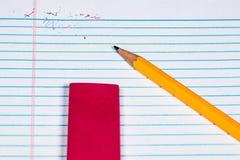 Ein gelöschtes Wort auf einem Blatt Papier Ringbucheinlage mit dem Bleistift und äh Lizenzfreie Stockbilder