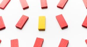 Ein gelber Holzklotz unter den roten stockbild