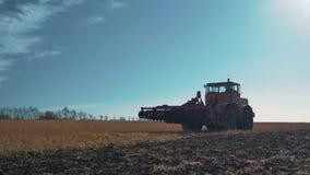 ein gelber Traktor bewegt sich über ein gepflogenes Feld im Fall, um zu ernten stock footage
