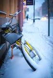 Ein gelbes Fahrrad auf einer Stadtstraße im Winter Stockbilder