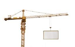 Ein gelbes hochziehendes Kran und Anzeige hoardin Stockbild