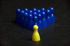 Ein gelbes Pfand und Gruppe blaue Pfand auf einer Tabelle Lizenzfreie Stockbilder