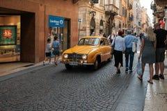 Ein gelbes Retro- Auto Saab reitet durch eine Menge von Touristen entlang der schmalen Straße von Verona lizenzfreie stockfotos