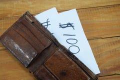 Ein Geldbeutel auf dem Tisch und in ihm ein Papier mit der Aufschrift Stockfotografie