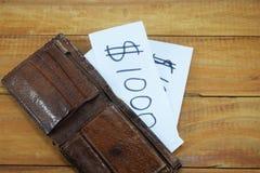 Ein Geldbeutel auf dem Tisch und in ihm ein Papier mit der Aufschrift Lizenzfreie Stockfotografie