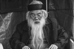 Ein Gelehrter schreibt chinesische Kalligraphiecharaktere am Tempel der Literatur Stockbild