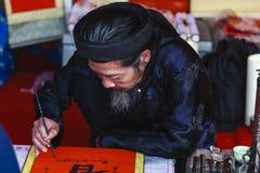Ein Gelehrter schreibt chinesische Kalligraphiecharaktere am Tempel der Literatur Lizenzfreie Stockfotografie