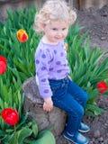 Ein gelocktes blondes Baby und Tulpen Lizenzfreie Stockbilder