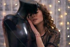 Ein gelocktes dunkelhaariges Mädchen umarmt ein Mannequin und Umarmungen bis zu ihm mit ihren geschlossenen Augen Das Konzept der stockbild