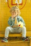 Ein gelocktes Mädchen sitzt an einer Bushaltestelle Lizenzfreie Stockbilder