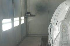Ein gemaltes weißes Auto in einem Standspray Lizenzfreies Stockfoto