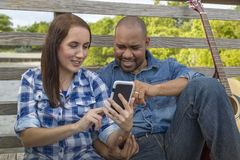Ein gemischtrassiges Paar sitzt auf einer Plattform mit einem Smartphone stockfotografie