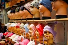 Ein Geschäft mit Baby- und Kindkappen auf den Köpfen der Puppe stockfotografie