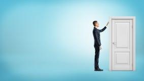 Ein Geschäftsmann auf blauem Hintergrund berührt einen weißen Türrahmen mit einer geschlossenen Tür nach innen Lizenzfreies Stockbild