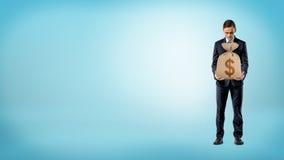 Ein Geschäftsmann auf dem blauen Hintergrund, der eine Leinwandgeldtasche mit einem Dollarzeichen auf ihm hält Stockfotografie