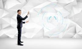 Ein Geschäftsmann auf weißem geometrischem Wandhintergrund einen VR-Schirm manipulierend Stockfoto