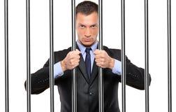 Ein Geschäftsmann in den Gefängnisholdingstäben Stockfotos