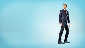 Ein Geschäftsmann, der auf blauem Hintergrund in der halben Drehung steht und über seiner Schulter schaut Stockfotografie