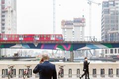 Ein Geschäftsmann, der auf dem Mobile beim Gegenüberstellen des mittleren Docks spricht lizenzfreie stockfotografie