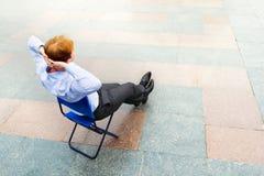 Ein Geschäftsmann, der auf der Straße sich entspannt lizenzfreie stockfotos