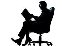 Ein Geschäftsmann, der in der Lehnsessellesung sitzt Stockbilder