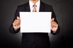 Ein Geschäftsmann, der ein Papier vor seinem Gesicht hält Stockfotografie