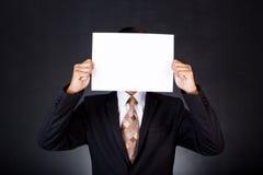 Ein Geschäftsmann, der ein Papier vor seinem Gesicht hält Stockbild