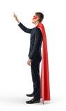 Ein Geschäftsmann, der ein rotes Superheldkap steht in der Seitenansicht und verwendet ein unsichtbares mit Berührungseingabe Bil Lizenzfreie Stockfotos