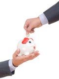 Ein Geschäftsmann, der eine Münze in eine piggy Querneigung setzt stockbilder
