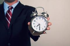 Ein Geschäftsmann, der eine Uhr hält stockfotos