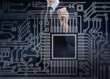 Ein Geschäftsmann, der einen Elektronikstromkreis berührt Stockbilder