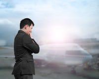 Ein Geschäftsmann, der Flugzeug einem Flughafen betrachtet Stockfotografie
