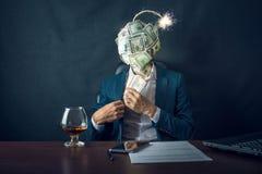 Ein Geschäftsmann, der Geld in seine Tasche mit einer Bombe in Form von BallDollarscheinen anstelle seines Kopfes einsetzt lizenzfreies stockbild