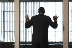 Ein Geschäftsmann, der heraus innen durch eine Glaswand schaut Lizenzfreies Stockbild