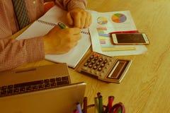 ein Geschäftsmann, der im Hauptbürotischplan für Geschäftsmöglichkeitsanalyse arbeitet Mannhand mit Taschenrechner am Arbeitsplat Stockbild