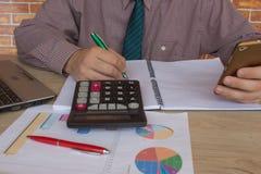 ein Geschäftsmann, der im Hauptbürotischplan für Geschäftsmöglichkeitsanalyse arbeitet Mannhand mit Taschenrechner am Arbeitsplat Stockfoto