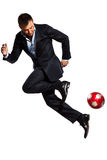 Ein Geschäftsmann, der jonglierende Fußballkugel spielt Stockfotografie