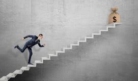 Ein Geschäftsmann, der oben ein konkretes Treppenhaus mit einer gebundenen Tasche des groben Sackzeugs mit einem Dollarzeichen au Lizenzfreies Stockbild