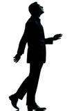Ein Geschäftsmann, der Schattenbild oben schauend geht Stockfoto