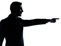 Ein Geschäftsmann, der Schattenbild zeigt Stockbilder