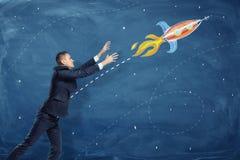 Ein Geschäftsmann, der seine Hände zu einem Fliegen durch die Himmelrakete gemalt auf einer Tafel hochzieht Lizenzfreies Stockfoto
