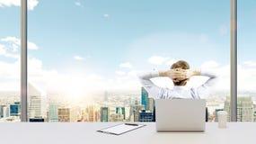 Ein Geschäftsmann, der in seinem Büro sich entspannt Stockfotos