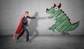 Ein Geschäftsmann in einem roten Kap, das in der kämpfenden Haltung bereit, ein Bild eines Drachen auf der nächsten Wand zu kämpf Stockfoto