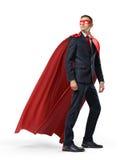 Ein Geschäftsmann in einem roten Kap des Helden und eine Maske in der Vorderansicht, die im Abstand über seiner Schulter auf weiß Lizenzfreie Stockfotos