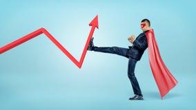 Ein Geschäftsmann in einem roten Superheldkap, das einen roten Statistikpfeil mit seinem Fuß schlägt Lizenzfreies Stockfoto
