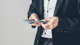 Ein Geschäftsmann in einem schwarzen LuxusAnzug hält Dollar in seinen Händen Der Mann zählt sein Geld stockfotos