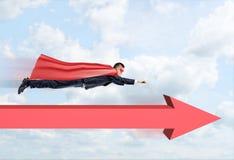 Ein Geschäftsmann in einem Superheldkap, das gerade durch die Wolken mit einem roten Pfeil unter ihn vorwärts zeigend fliegt Stockfotos