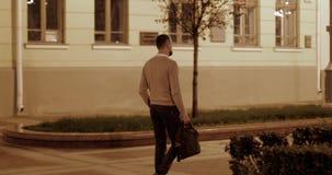 Ein Geschäftsmann in einer beige Jacke mit einer Tasche in seiner Hand geht durch die Nachtstadt stock video footage